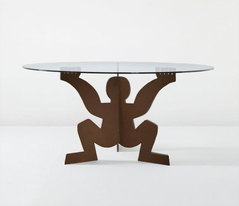 Dining table designed by Maurizio Cattelan in 1991 as a gift for Dilmos.  Composed of a glass top and a base in crude iron depicting the form of the
