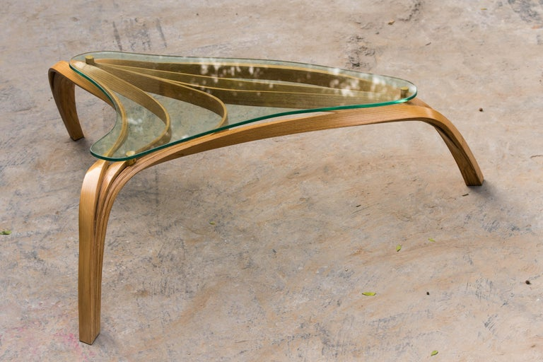 One of the Studio's earlier coffee table designs. A minimal design achieved by bending wood which reveals beautiful details at a closer look. The clear lacquer finish exposes the natural grains of wood along with its craftsmanship.   Our Vrksa