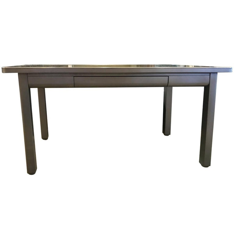 Industrial interior design showcases neutral tones, utilitarian objects, and wood and metal surfaces, proudly displaying the building materials that many try to conceal. Sleek and sophisticated, this brushed steel writing desk features a
