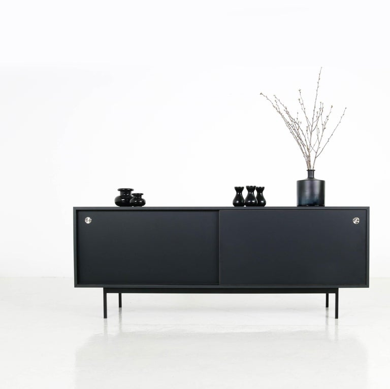Beautiful sideboard, freestanding, made in Germany, design by Nathan Lindberg (Nathan Lindberg Design) Black HPL (Formica) body in matte, with sliding doors in black (painted or formica covered in black, depending on stock) with stainless steel door