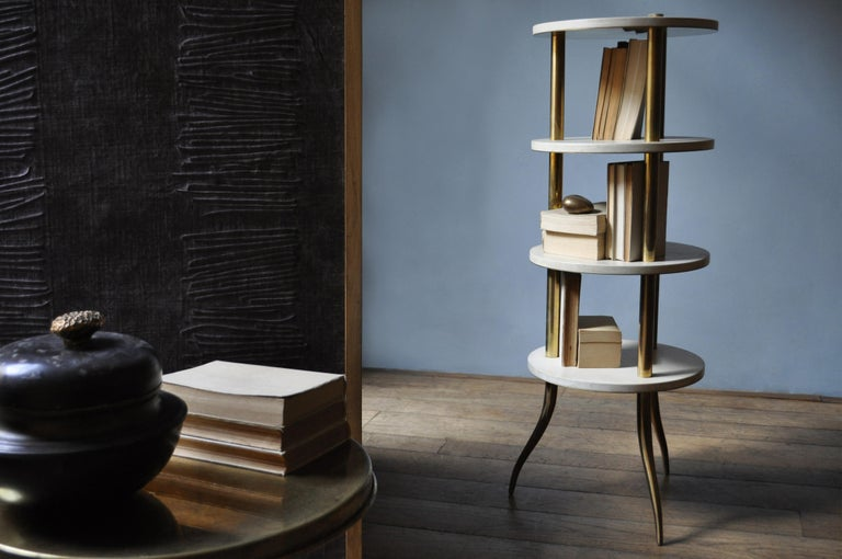Distinguished for its essential shape, freefrom superfluous elements, this column bookcase is characterized by soft colors of parchment leather and shiny brass that give it a retro charm. The structure in brass is made up of three columns with