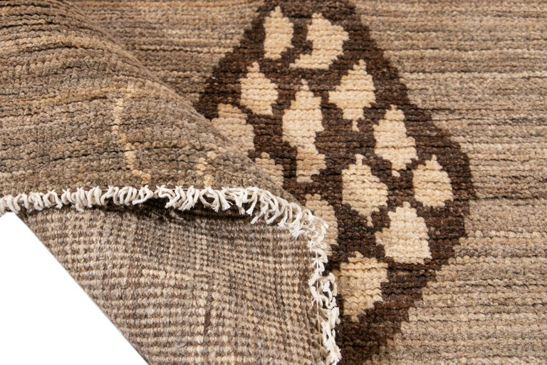 Beautiful Moroccan style hand knotted wool rug with a tan field. This rug has accents of brown in a gorgeous all-over Geometric tribal design.  This rug measures 8'10