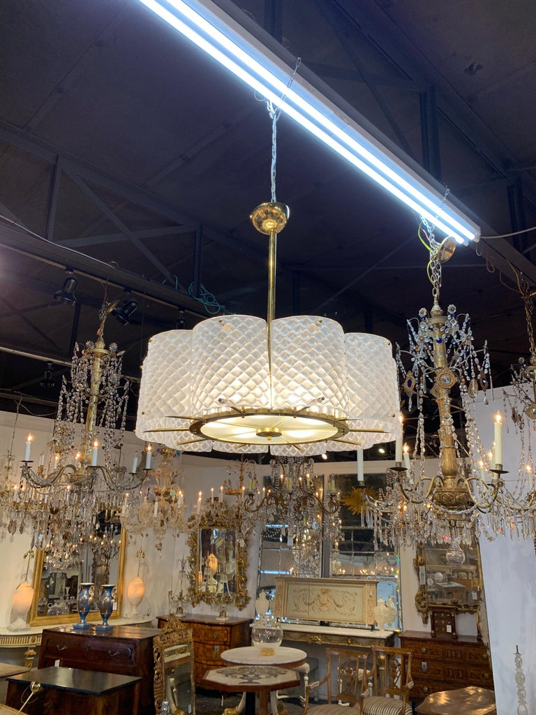 Stunning Murano glass and brass chandelier. Very pretty sections of white toned Murano glass with brass base. Notice the cylinders of glass inside the fixture adding additional interest. A great look for a modern home!