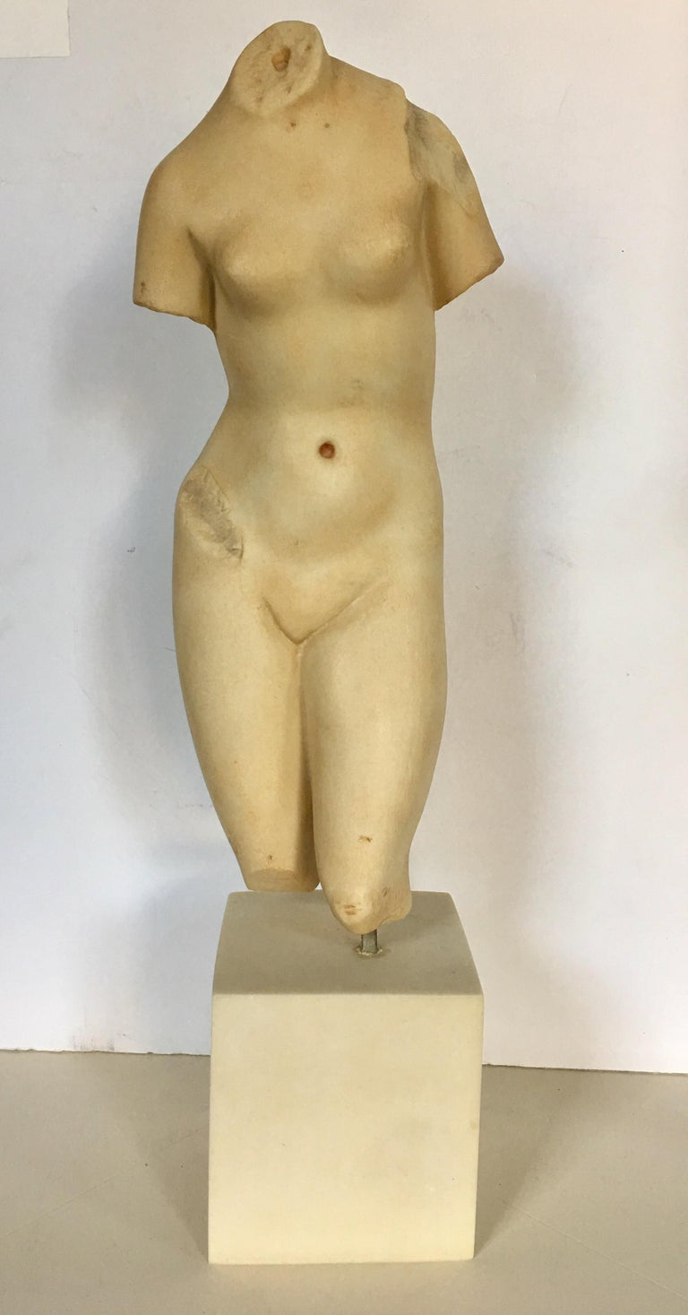 Modern Museum of Art sculptural reproduction of Aphrodite. This female form torso sculpture is constructed of a faux marble alabaster heavy weight resin and is mounted with a brass rod on a square plinth base. Beautiful tabletop accessory accent