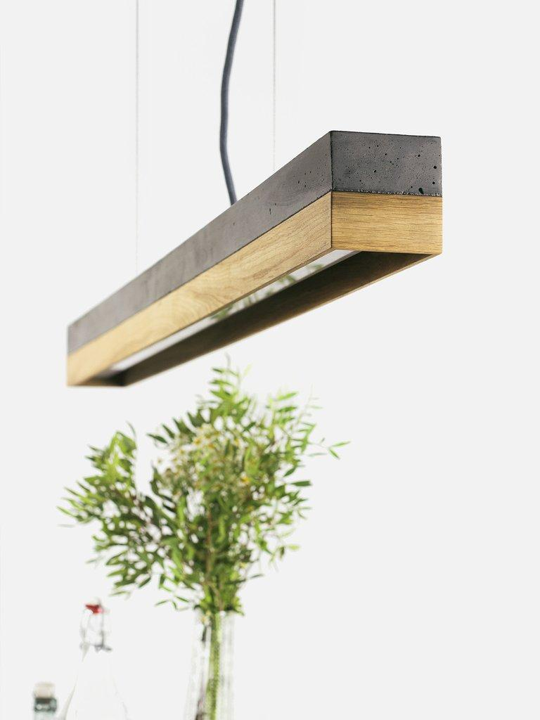 The rectangular pendant lamp [C1] is cast from a light grey concrete. It combines modern materials such as copper, brass, oakwood or corten steel with rough concrete into a timeless and elegant designer lamp. The different materials of the lamp