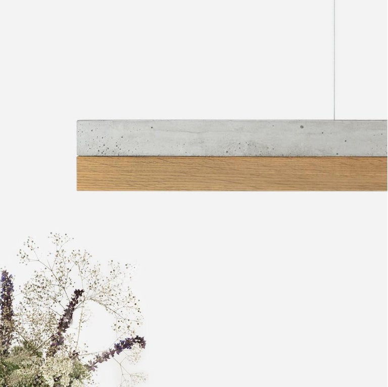 The rectangular pendant lamp [C1] is cast from a light grey concrete. It combines modern materials such as copper, brass, oak wood or corten steel with rough concrete into a timeless and elegant designer lamp. The different materials of the lamp