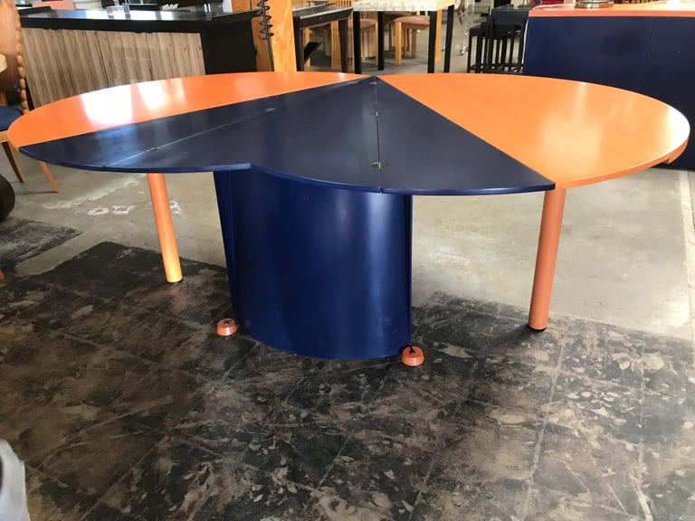 One of kind two-toned dining table in terracotta orange and navy blue stained wood, manufactured by Castelijn Meubelindustrie in the Netherlands.  It folds into a smaller round table (diameter: 51