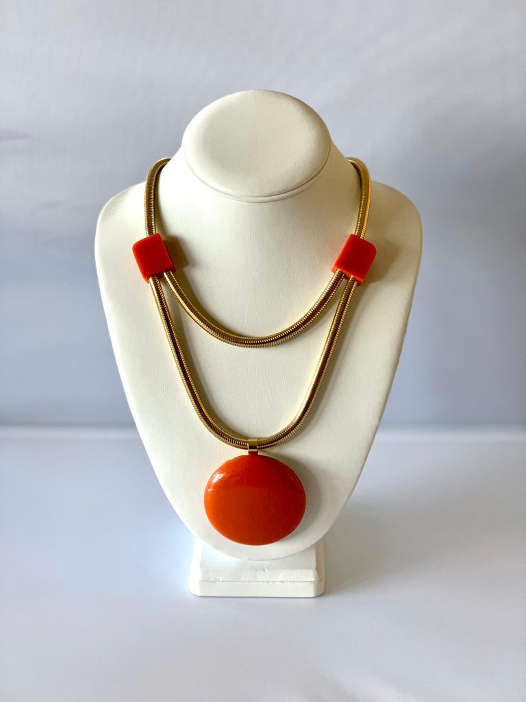 Modern orange Bakelite statement necklace by Castillo for Lanvin, Paris circa 1960 - the necklace is comprised out of a double gold snake chain which is adorned by three orange geometric phenolic elements. Two small squares and a large circular