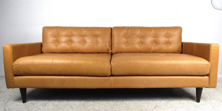 This beautiful contemporary modern sofa features four overstuffed removable tufted cushions. A comfortable a stylish piece that sits on stubby black tapered wood legs. An elaborate orange color that is sure to make a lasting impression in any