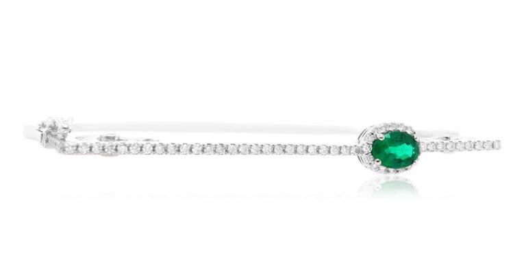 Material: 14K White Gold  Stone Details: 1 Oval Emerald at 0.8 Carats Total- Measuring 7 x 5 mm Diamond Details: 66 Brilliant Round Diamonds at 0.65 Carats- Clarity/ S-I: Color/ H-I  Fine one-of-a-kind craftsmanship meets incredible quality in this