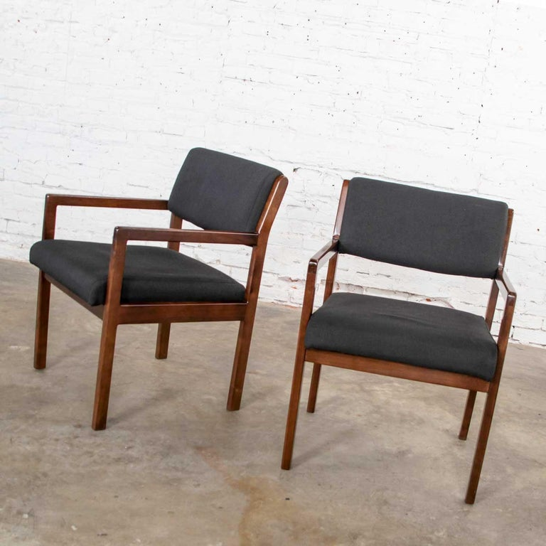 Handsome pair of walnut tone wood accent or dining armchairs with black wool-like fabric upholstery. They are in wonderful original condition. The fabric is nearly perfect. The walnut stained, we believe ash, wood does show signs of age and use but