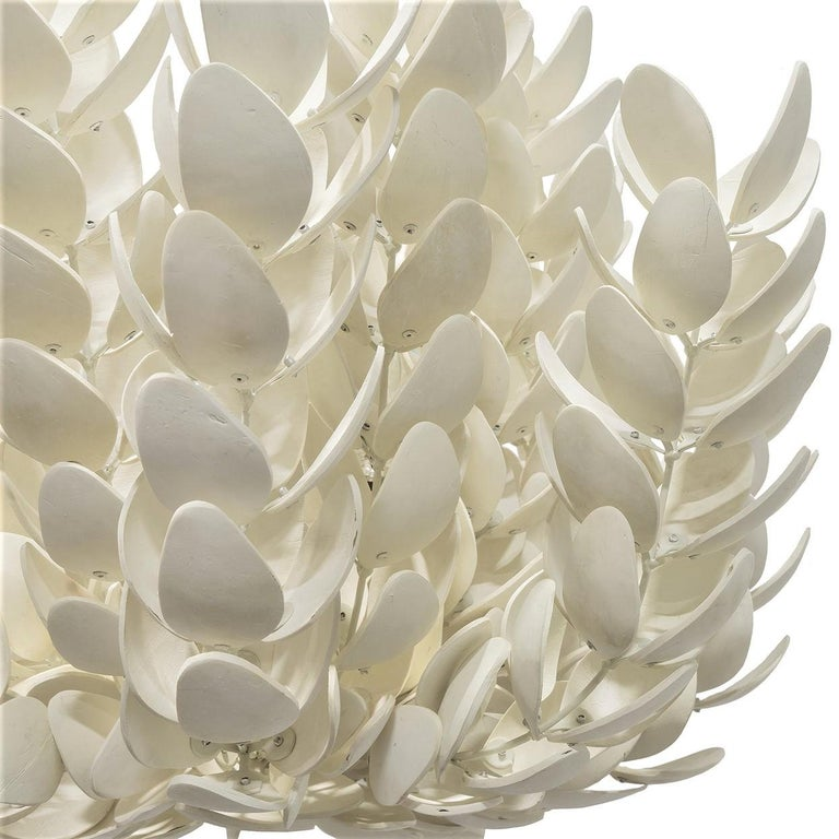 Organic modern pendant crafted of handcut shells in petal forms in an off-white finish.