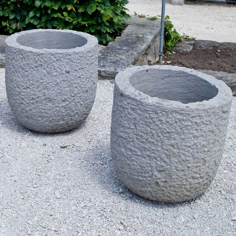 Pair of hand-carved, modern planters with a round base shape, a curved wall and a rough hammered surface out of bluestone.
