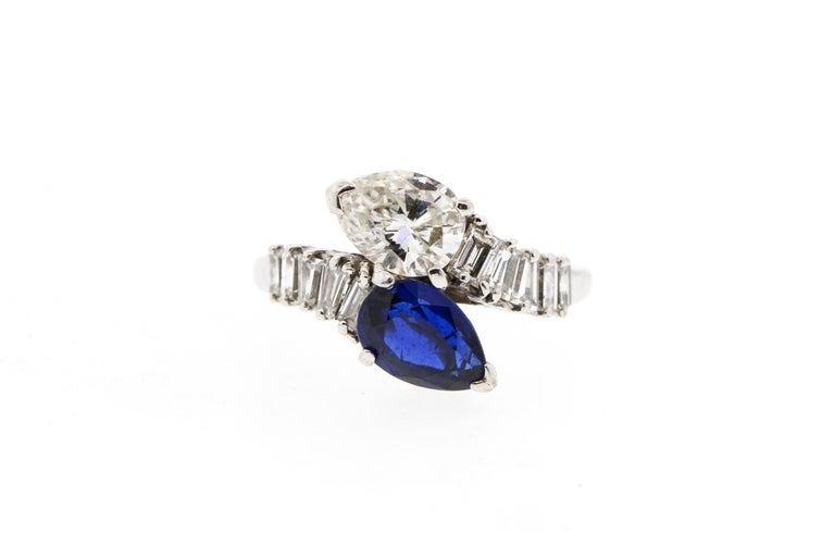 A mid-century platinum sapphire and diamond bypass ring, circa 1960. The ring is set with a white pear shape diamond weighing approximately 1.15 cts and an opposing blue sapphire weighing about the same. The diamond is very clean and white,