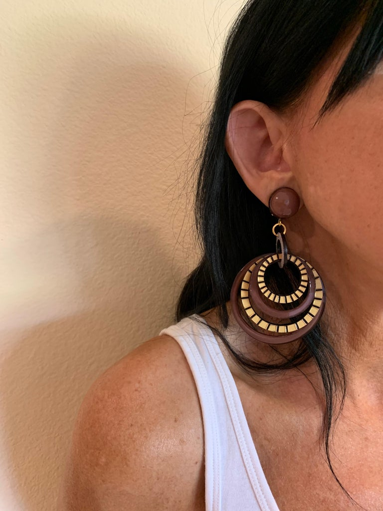 Light and easy to wear, these handmade artisanal hoop clip-on earrings were made in Paris by Cilea. The earrings are comprised of black, brown and gold enameline (resin and enamel composite) and depict three-dimensional pop art circles. Throughout