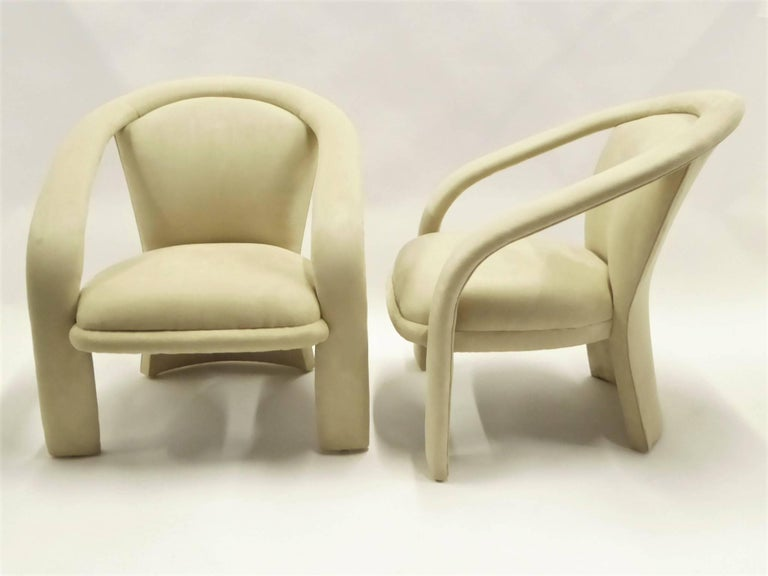 Sporting modern wrap around arms and a fan shaped back, this pair of lounge chairs by Carson's owes inspiration to Milo Baughman. This mid-1980s design newly upholstered in a cream Ultrasuede. Stunning, comfy and late Mid-Century Modern, Space