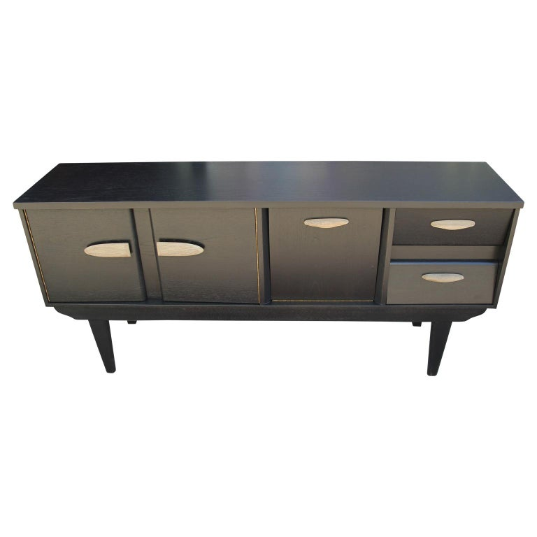 Wonderful modern custom sideboard or credenza newly restored with a black finish and wooden handles. The drawers make a fun accent with angled front panels. This sideboard has two drawers, one middle drop front cabinet, and a larger second cabinet