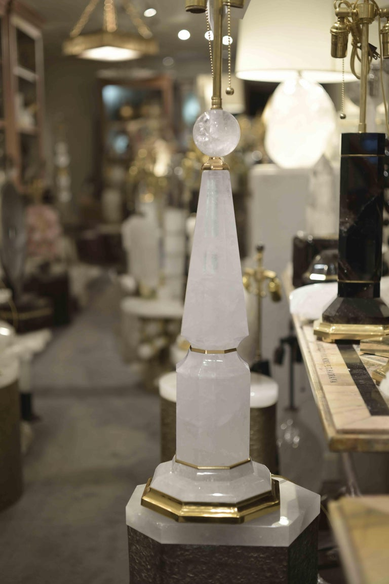 Pair of fine carved prism and column-form rock crystal lamp with polished brass bases, created by Phoenix Gallery, NYC. Available in nickel plating and antique brass finished.  To the top of the rock crystal: 24