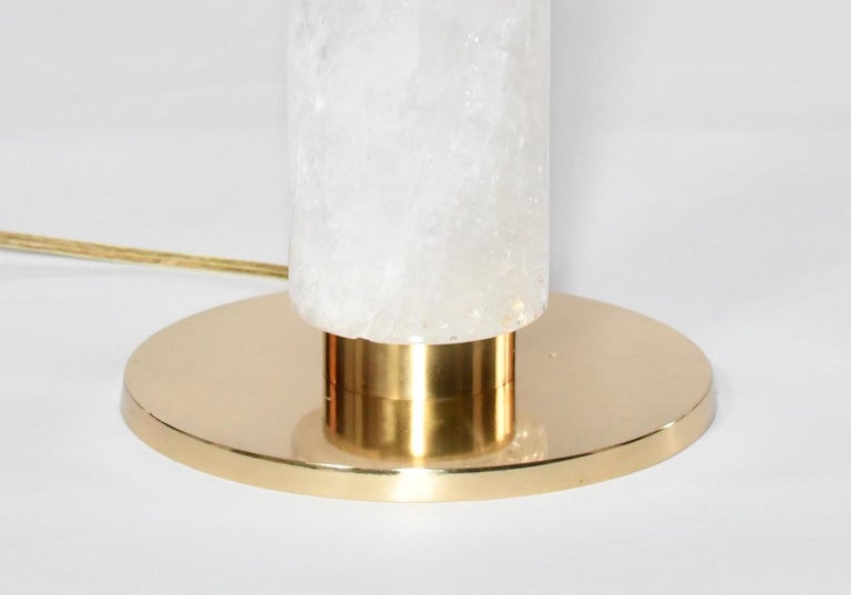 A fine carved cylindrical form of rock crystal quartz lamp with polished brass base. Available in antique brass finish and nickel-plating, created by Phoenix Gallery, NYC. To the rock crystal: 15