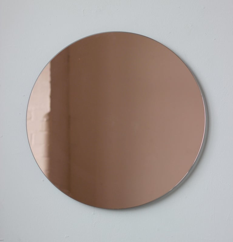 Delightful crafted peach tinted / rose gold tinted round mirror frameless with a floating effect. Design and handcrafted in London UK.   Supplied fully fitted with a specialist hanging system for an easy installation.  Also available