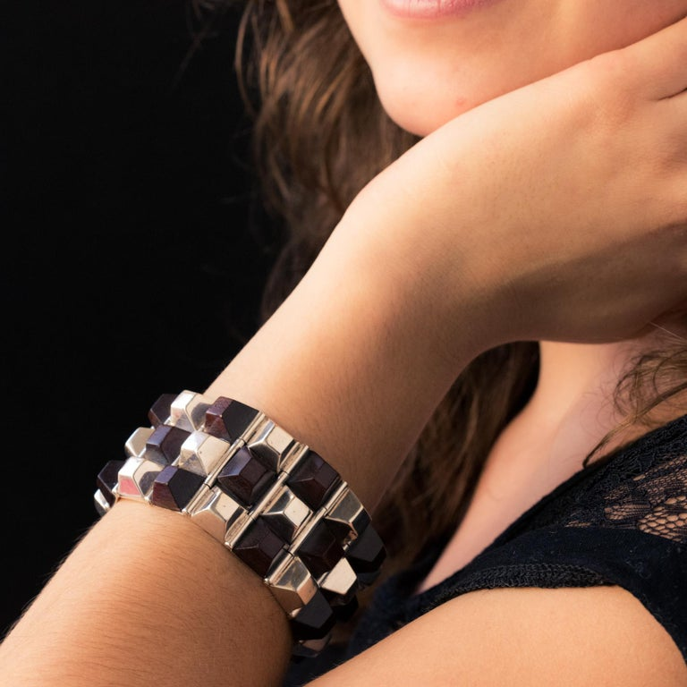 Bracelet in silver. Geometric shaped, this incredible cuff bracelet is made up of rectangular patterns hinged together. Each is set on top of an alternation of silver and rosewood pyramids. The clasp is hinged with safety clip. Length: 19.5 cm,