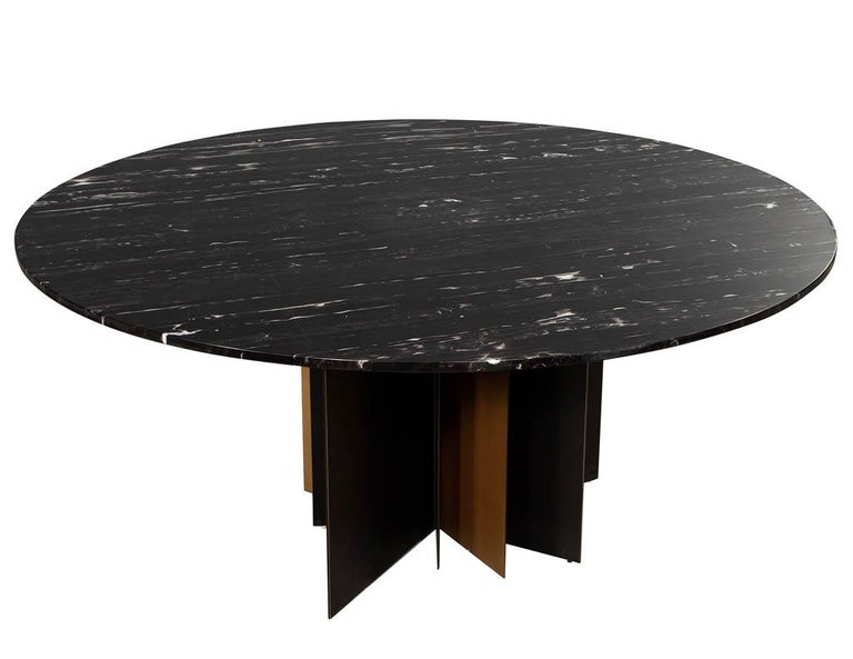 Modern round black marble top dining table. Featuring unique modern starburst metal pedestal with 3/4