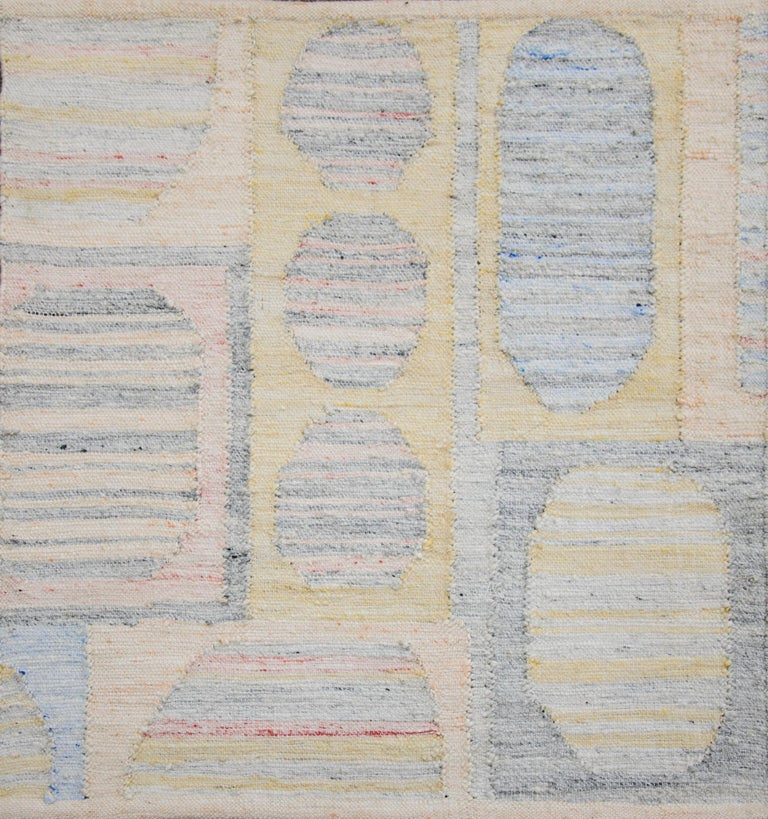Modern area rug handwoven in Scandinavian design using fine wool and organic dyes. It features an exquisite gray striped field with colorful geometric patterns all-over. This piece will surely look fabulous in modern and contemporary interiors. It