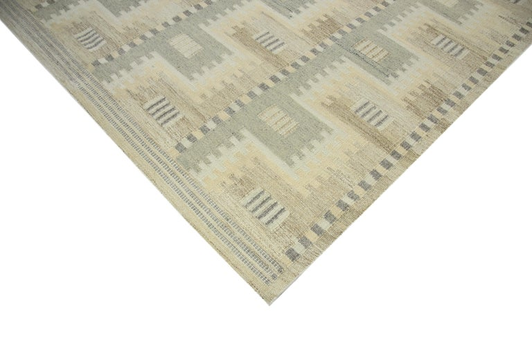Modern area rug is handwoven in Scandinavian design using fine wool and organic dyes. It features an exquisite ivory field with geometric patterns in gray and brown. This piece will surely look fabulous in modern and contemporary interiors. It has a