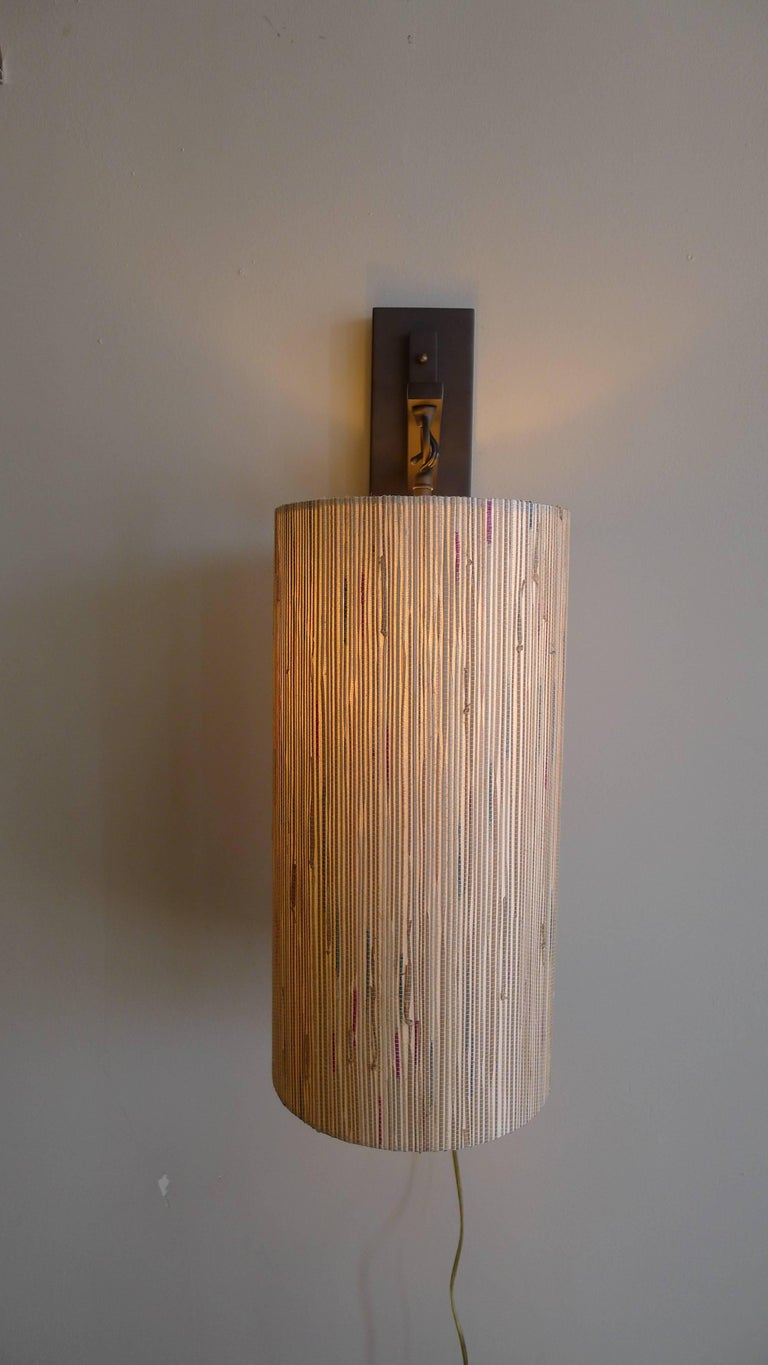 Modern sconce in oil rubbed bronze metal with custom grass cloth shade by Paul Marra. Currently a pair available, or by order. The custom shade is made of grasscloth in subtle colors. Price is per each sconce. Shade 16 x 8