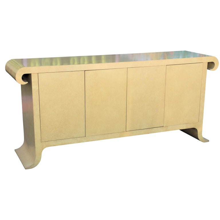 Modern cream colored scroll top sideboard or credenza designed by Alessandro Gambrielli for Baker Furniture in the style of Karl Springer. The case features two pull out drawers on the left and an adjustable shelf on the right.