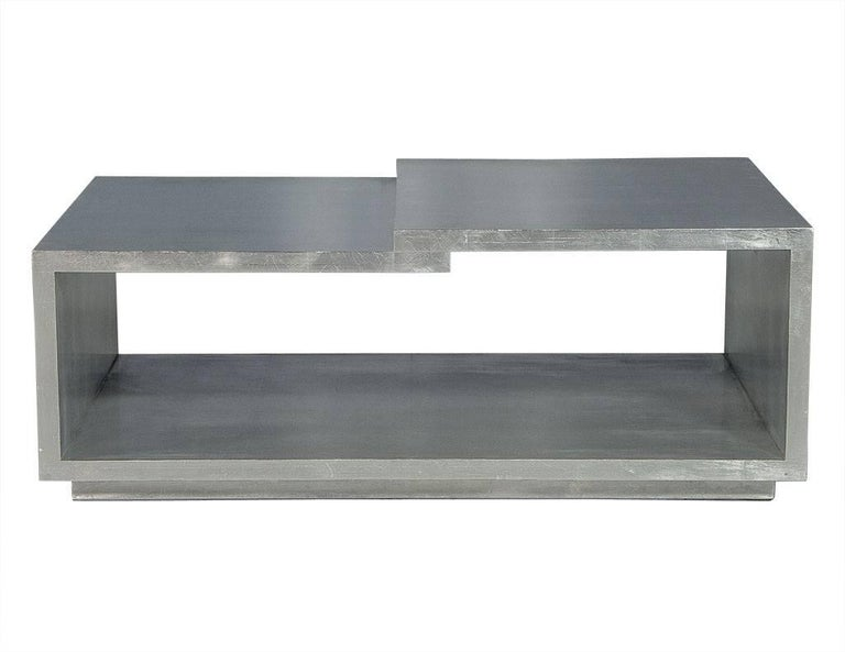 This modern cocktail table has a gorgeous, silver leaf brushed metal finish and open rectangular design. There are two levels to the top surface, one recessed, and the whole piece is full of character. A perfect addition to a luxe living