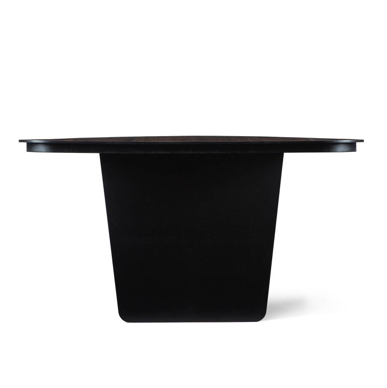 Carbon Claro, lightweight at the sight, robust in the structure. The Carbon Claro table features a precious solid charred claro walnut combined top with thin carbon legs in different color finishes. The two elements connect seamlessly in a