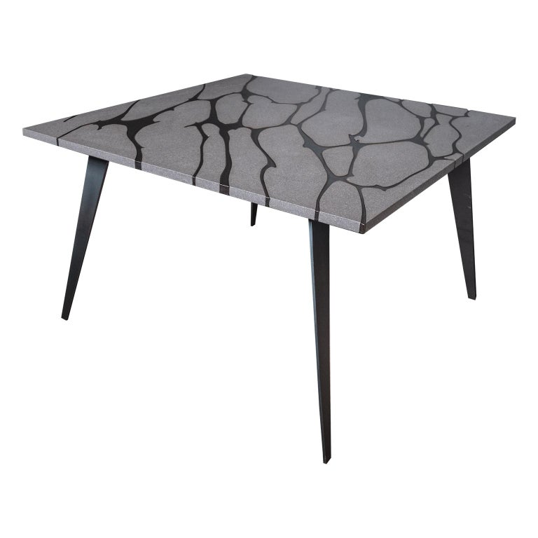 Filodifumo is a contemporary square outdoor table with top in lava stone and steel legs. It is made with solid and compact matter. High precision machinaries engrave on the lava stone surface