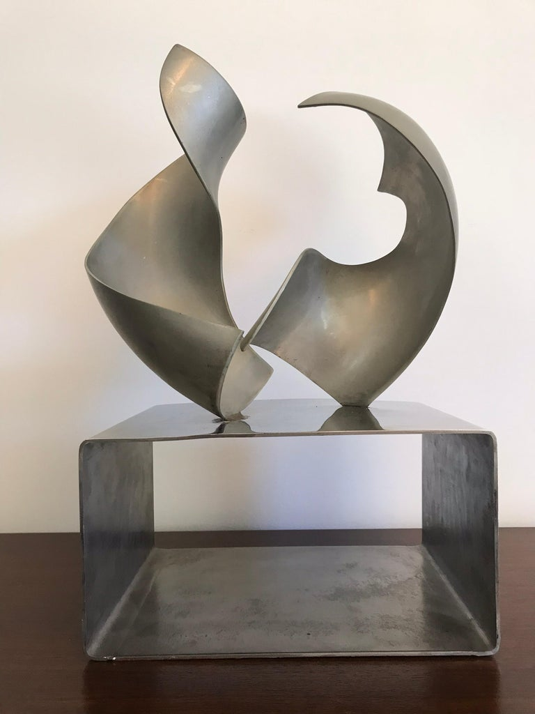 A nice modernist design. Made of stainless and polished steel, showing two abstract forms on an architectural base that appears to be part of the pieces in space. Not signed.