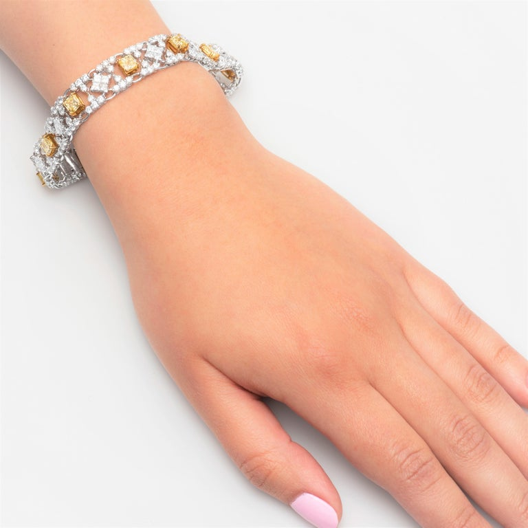 Modern style bracelet with 10 natural radiant cut fancy yellow diamonds weighing 6.20 carats total surrounded by 9.99 carats of white diamonds. The yellow diamonds are set in 18K yellow gold and white diamonds are set in platinum.   White diamond
