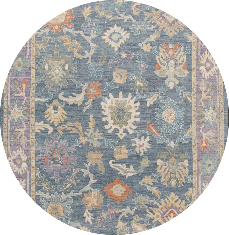 Beautiful contemporary Sultanabad rug, hand knotted wool with a blue field. This rug has a frame of purple and multi-color accents in all-over Classic floral medallion design.  This rug measures: 9'8