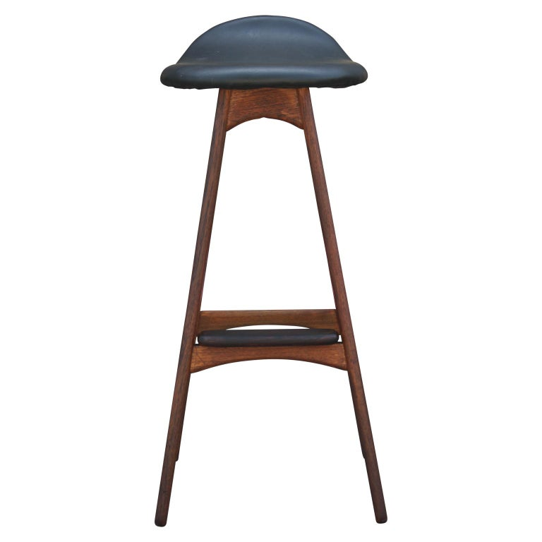Modern and sleek teak and black leather bar stool with a rosewood foot rest designed by Erik Buck for Odense Møbler. Model OD61.