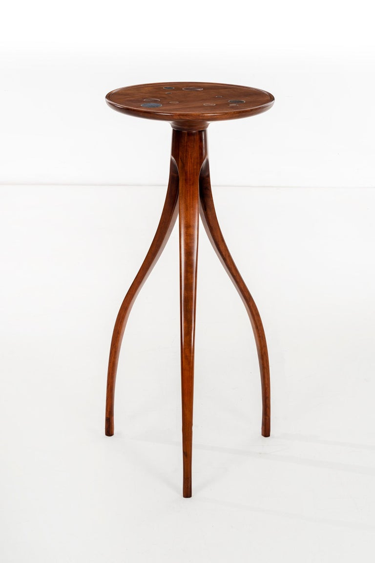 Slender scale pedestal high tripod table, solid carved walnut lip edge top with ceramic design details inset. Feet have lighter tone wood accent.