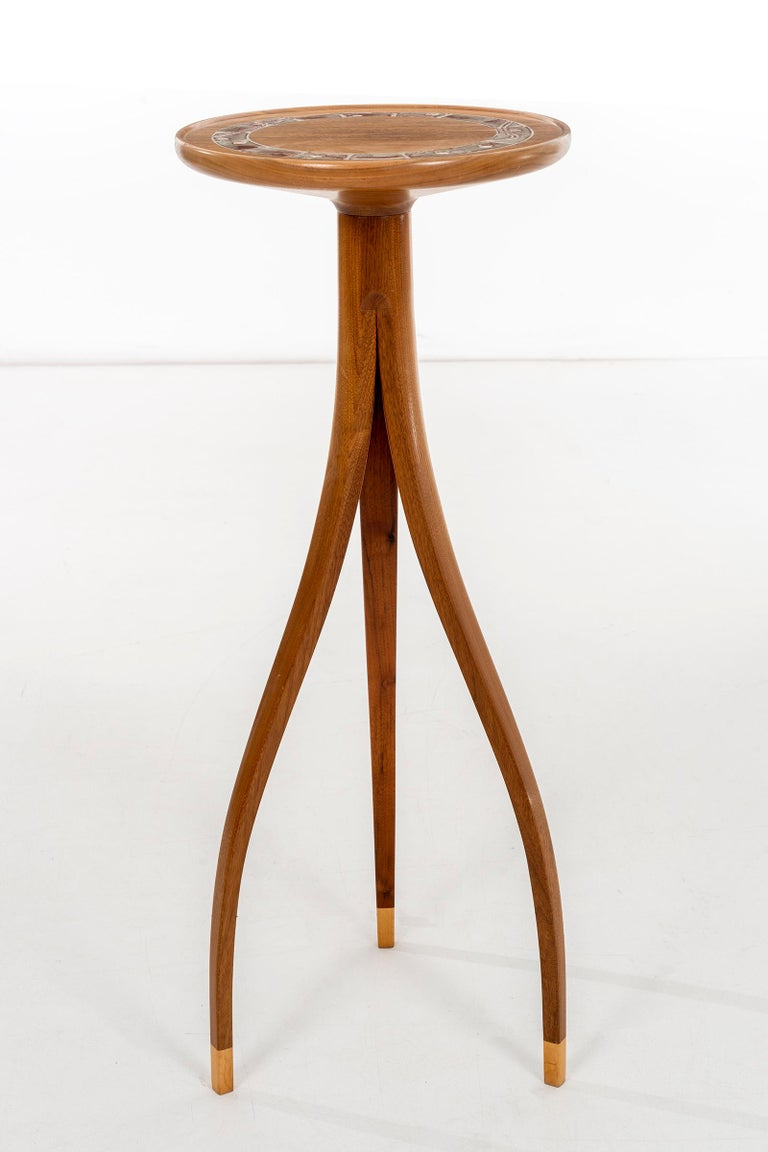 Slender scale high tripod table, solid carved walnut lip edge top with ceramic design detail inset. Feet have lighter tone wood accent.