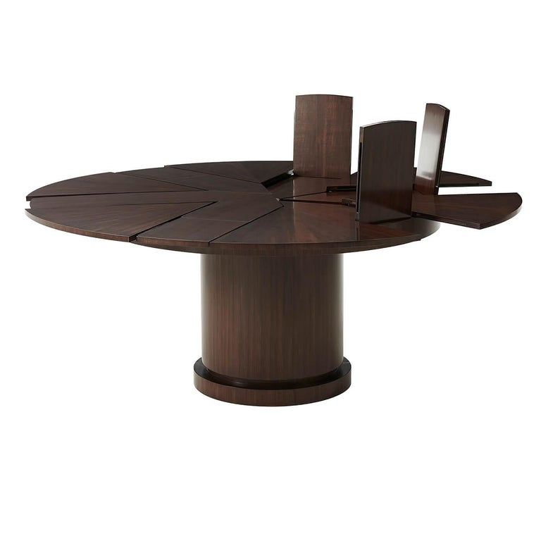 A Mid-Century Modern style round pacific walnut extension dining table with self-storing fold-out leaves on a bold cylindrical column pedestal base.  Dimensions: Open: 72