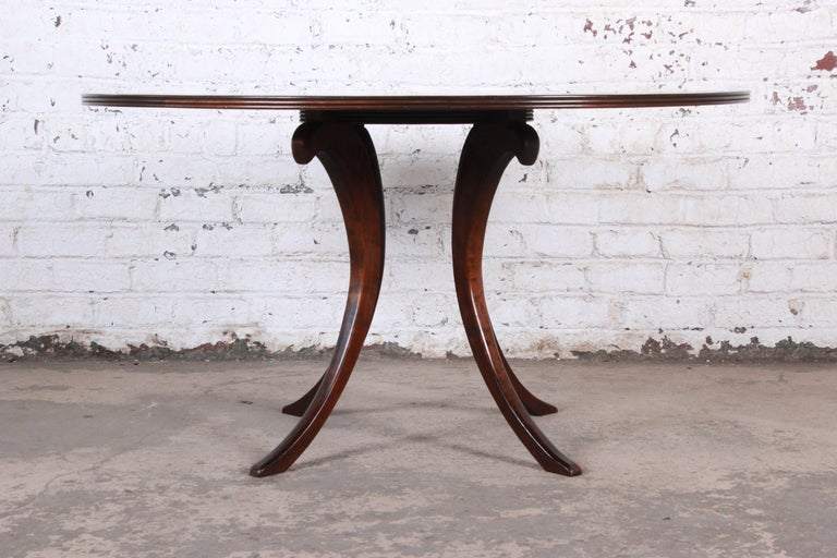 A gorgeous modern walnut saber leg dining table with inlaid starburst parquetry top  Late 20th century  Measures: 54.75