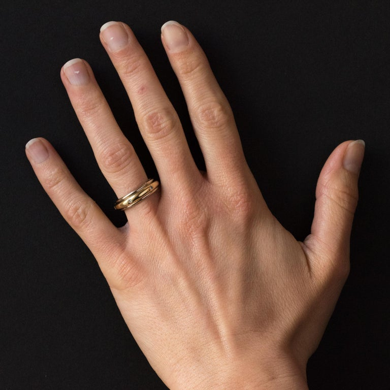 Ring in 18 karats white gold and yellow gold. 2 golds ring, it consists of a wide yellow gold ring set with 6 brilliant- cut diamonds spread throughout its turn. This yellow gold part is inserted in a white gold rail and turns on the finger. Total