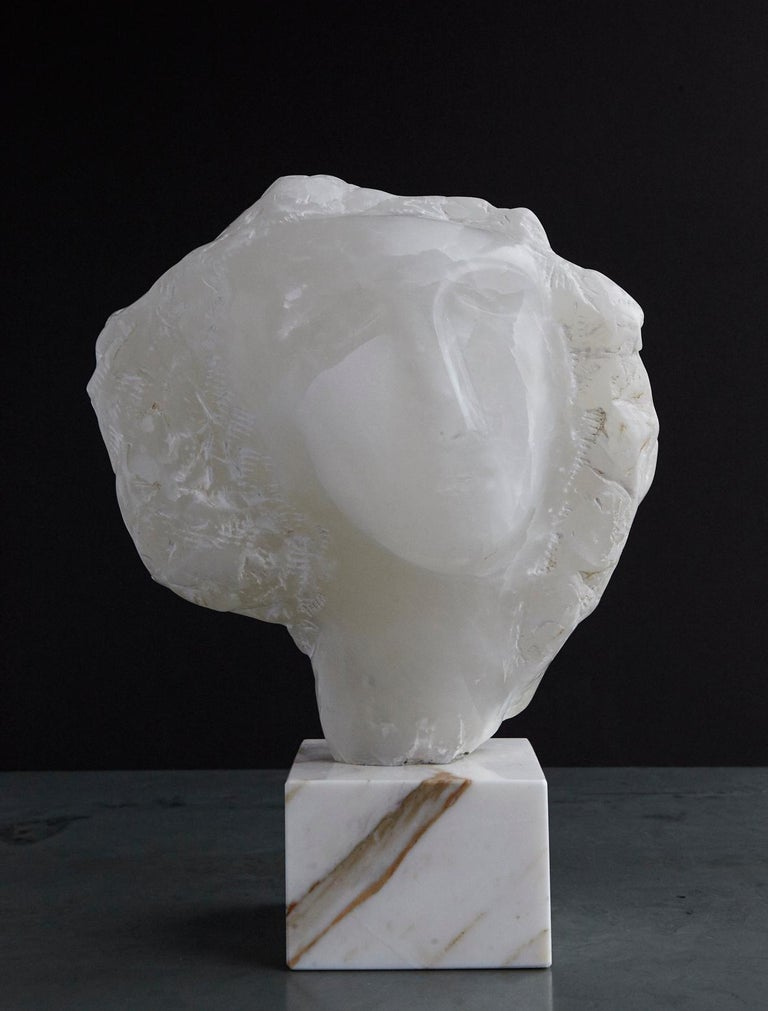 Beautiful modern white onyx sculpture of a woman's face mounted on a square marble base. Depending of the placement of the piece, the sculpture seems to glow when it is backlit through a window light, please see photos. Measurements: Sculpture: H