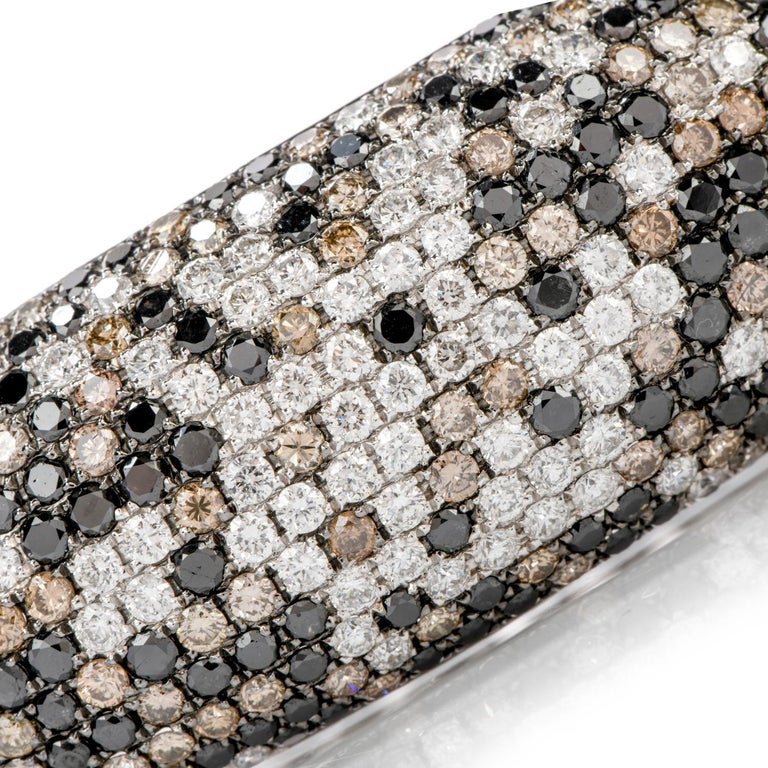 This scrumptious and delightfully tasteful twist on   a classic bangle bracelet features bold colors of metal and diamonds.  Black, White and Champagne colored diamonds, in a random pattern, are the focal point  of this exquisite 18K gold