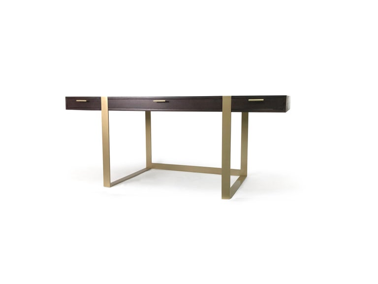 This modern writing desk was custom made for utility. The desk features 3 drawers for storage, a steel base brushed with antique brass and a white oak top stained ebony. This is a built to order piece and can be made to your specifications with your
