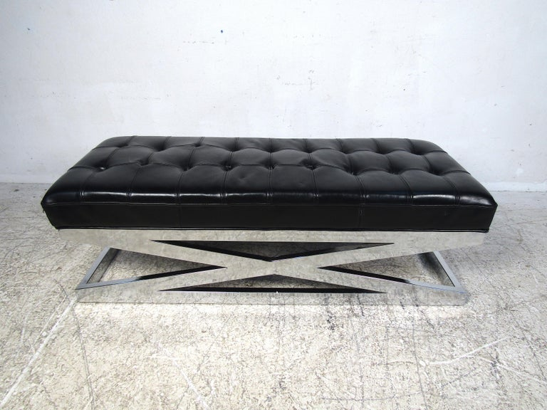 Stylish modern upholstered bench. Sturdy X-frame chrome base. The padded seat is covered in a black tufted faux-leather upholstery. A nice piece that is sure to compliment any modern interior. Please confirm item location with dealer (NJ or NY).