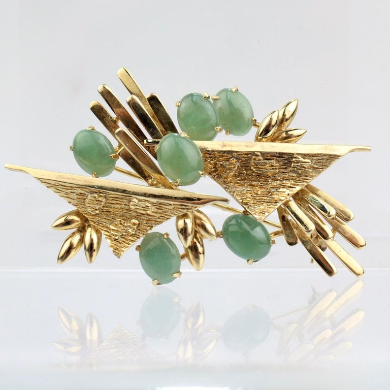 A wonderful 18k gold and nephrite jade brooch.   With textured gold devices flanked offset with 6 jade cabochons.   Simple & visually exciting modernist design!  Marked 18K to the reverse.  Length: ca. 55 mm  Items purchased from this dealer must
