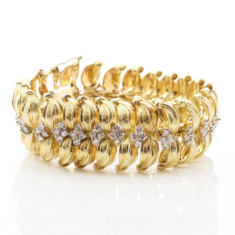 This Modernist bracelet features yellow gold leaf inspired link designs, each one containing 4 round brilliant cut diamonds. There are a total of 100 round diamonds, which weigh a combined total of approximately 7.00ctw and grade as