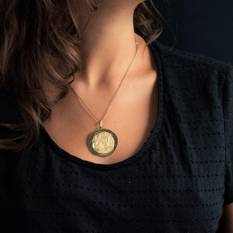 Medal in 18 karat yellow gold. On its front, this medal represents the Crowned Virgin with the infant Jesus holding the terrestrial globe. On the back is a cross surrounded by stars. Diameter : 3.5 cm, widest thickness : about 1 mm. Total weight of