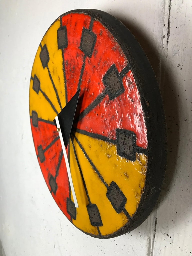 Eye-catching modernist Italian ceramic wall clock by Bitossi (Italian potter) manufactured by Howard Miller using hands designed by Goerge Nelson (American designer). This desirable glaze has brilliant red and orange colors and a sgraffito technique
